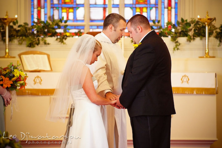 The officiant, the reverend, is giving blessing to the bride and groom. Kent Island Methodist Church KIUMC Wedding Photographer Maryland