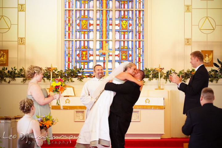 Groom lift bride off the ground. Pastor and guests laugh. Kent Island Methodist Church KIUMC Wedding Photographer Maryland