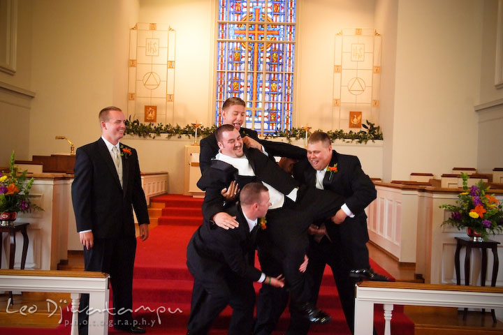 Best man and groomsman trying to lift up groom. Kent Island Methodist Church KIUMC Wedding Photographer Maryland