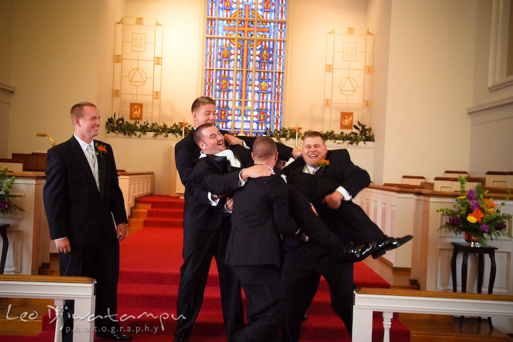Best man and groomsman attempting to lift up groom, laughing. Kent Island Methodist Church KIUMC Wedding Photographer Maryland