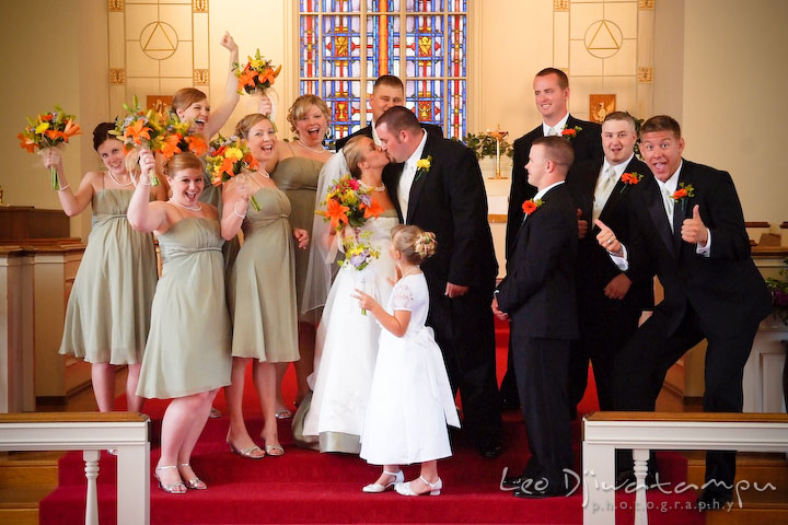 Best man, groomsmen, maid of honor, bridesmaids, and flower girl cheering at the kissing bride and groom. Best man and groomsman trying to lift up groom. Kent Island Methodist Church KIUMC Wedding Photographer Maryland