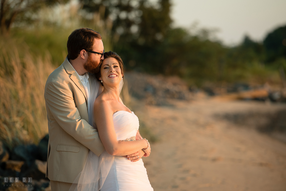 Eastern Shore Maryland Bride cuddling with Groom on the beach during sunset over the bay photo by Leo Dj Photography