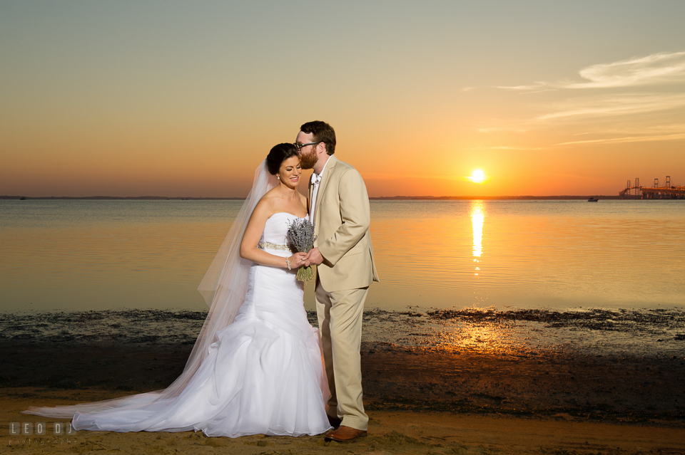 Chesapeake Bay Beach Club Groom kissing Bride during sunset over the bay photo by Leo Dj Photography