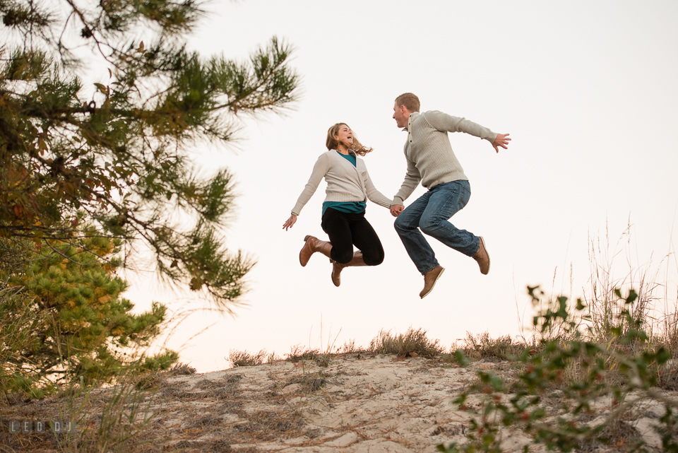 Cape Henlopen State Park Delaware engaged man jumping his fiancee for engagement photo by Leo Dj Photography.