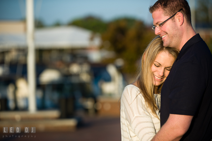 Engaged girl cuddling with her fiancé. Pre-wedding engagement photo session at Annapolis city downtown harbor, Maryland, Eastern Shore, by wedding photographers of Leo Dj Photography. http://leodjphoto.com