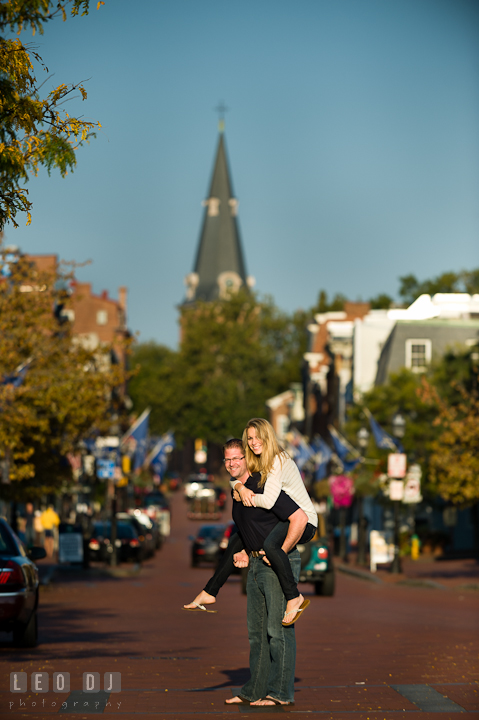 Engaged guy carrying his fiancée on his back. Pre-wedding engagement photo session at Annapolis city downtown harbor, Maryland, Eastern Shore, by wedding photographers of Leo Dj Photography. http://leodjphoto.com
