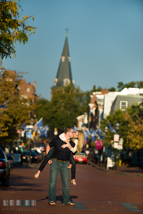Engaged girl kissing while carried on the back of her fiancé. Pre-wedding engagement photo session at Annapolis city downtown harbor, Maryland, Eastern Shore, by wedding photographers of Leo Dj Photography. http://leodjphoto.com