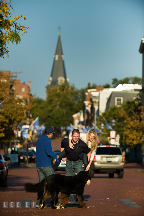 Engaged couple playing with stranger dog. Pre-wedding engagement photo session at Annapolis city downtown harbor, Maryland, Eastern Shore, by wedding photographers of Leo Dj Photography. http://leodjphoto.com