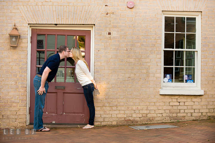 Engaged couple kissing by a brown door. Pre-wedding engagement photo session at Annapolis city downtown harbor, Maryland, Eastern Shore, by wedding photographers of Leo Dj Photography. http://leodjphoto.com