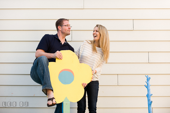 Engaged guy doing goofy pose, fiancé laughing. Pre-wedding engagement photo session at Annapolis city downtown harbor, Maryland, Eastern Shore, by wedding photographers of Leo Dj Photography. http://leodjphoto.com