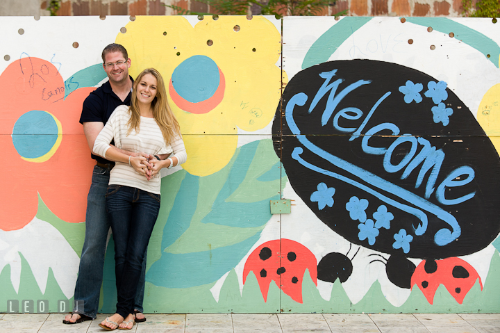 Engaged couple posing by a welcome wall mural. Pre-wedding engagement photo session at Annapolis city downtown harbor, Maryland, Eastern Shore, by wedding photographers of Leo Dj Photography. http://leodjphoto.com
