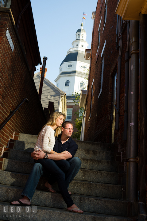 Engaged couple sitting on a stair with the Maryland State House in the background. Pre-wedding engagement photo session at Annapolis city downtown harbor, Maryland, Eastern Shore, by wedding photographers of Leo Dj Photography. http://leodjphoto.com