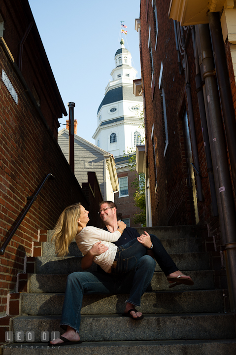 Engaged girl playing with her fiance on stairs with Maryland State House in the background. Pre-wedding engagement photo session at Annapolis city downtown harbor, Maryland, Eastern Shore, by wedding photographers of Leo Dj Photography. http://leodjphoto.com