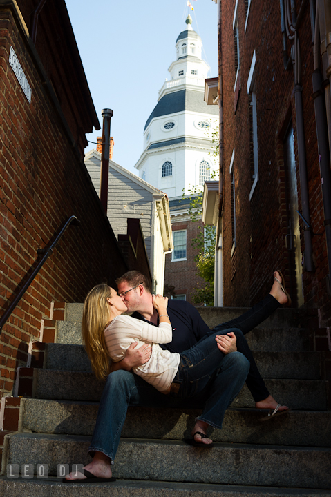 Engaged guy kissing his fiancee with Maryland State House in the background. Pre-wedding engagement photo session at Annapolis city downtown harbor, Maryland, Eastern Shore, by wedding photographers of Leo Dj Photography. http://leodjphoto.com