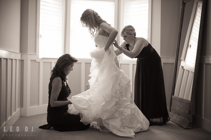 Maid of Honor and Mother of Bride helping putting on wedding gown on Bride. Kent Island Maryland Chesapeake Bay Beach Club wedding ceremony and getting ready photo, by wedding photographers of Leo Dj Photography. http://leodjphoto.com
