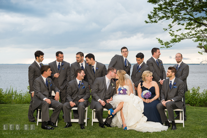 Bride and Groom kissed while Best Man, Maid of Honor, Man of Honor, and Groomsmen talking with each other. Kent Island Maryland Chesapeake Bay Beach Club wedding reception party photo, by wedding photographers of Leo Dj Photography. http://leodjphoto.com