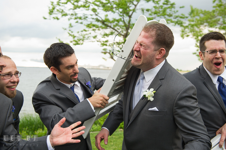 A groomsman hit Groom's head with a folding chair. Kent Island Maryland Chesapeake Bay Beach Club wedding reception party photo, by wedding photographers of Leo Dj Photography. http://leodjphoto.com