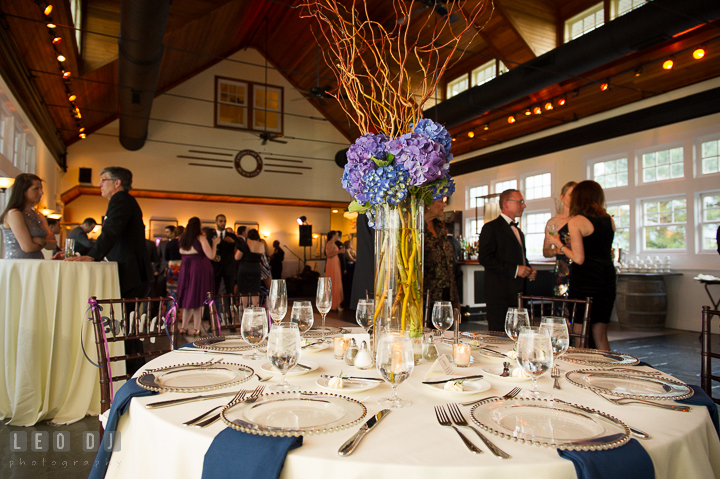 Bule and purple flowers in tall vase table centerpiece in Tavern Ballroom. Kent Island Maryland Chesapeake Bay Beach Club wedding reception party photo, by wedding photographers of Leo Dj Photography. http://leodjphoto.com