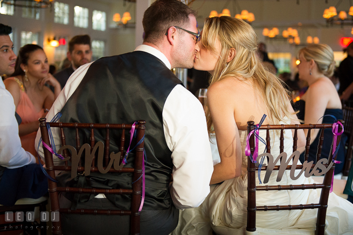 Bride and Groom kissing at their table. Metal Mr and Mrs sign on their chair. Kent Island Maryland Chesapeake Bay Beach Club wedding reception party photo, by wedding photographers of Leo Dj Photography. http://leodjphoto.com