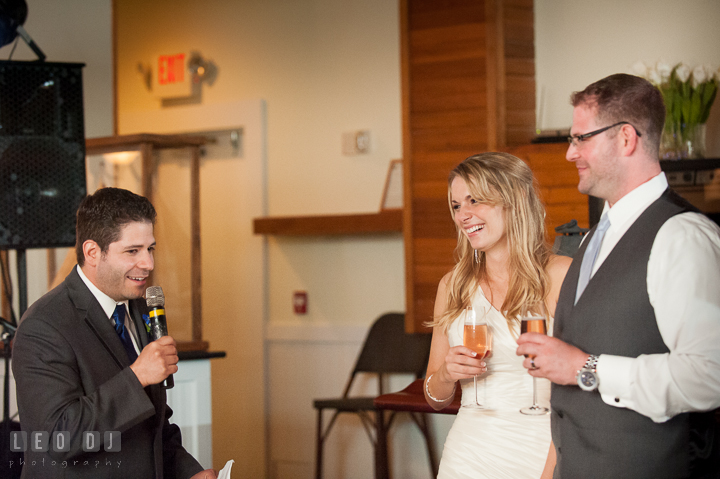 Bride and Groom laughing listening to Best Man's speech. Kent Island Maryland Chesapeake Bay Beach Club wedding reception party photo, by wedding photographers of Leo Dj Photography. http://leodjphoto.com