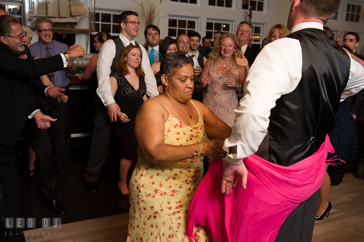Lady guest wrap her pink scarf around Groom's butt while dancing. Kent Island Maryland Chesapeake Bay Beach Club wedding reception party photo, by wedding photographers of Leo Dj Photography. http://leodjphoto.com