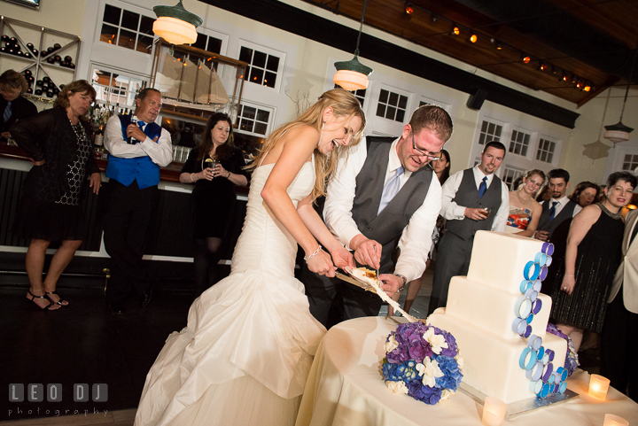 Bride and Groom laughing trying to pull piece of the cake. Kent Island Maryland Chesapeake Bay Beach Club wedding reception party photo, by wedding photographers of Leo Dj Photography. http://leodjphoto.com