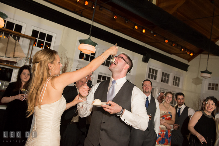 Bride aimed cake on Groom's nose while feeding him. Kent Island Maryland Chesapeake Bay Beach Club wedding reception party photo, by wedding photographers of Leo Dj Photography. http://leodjphoto.com