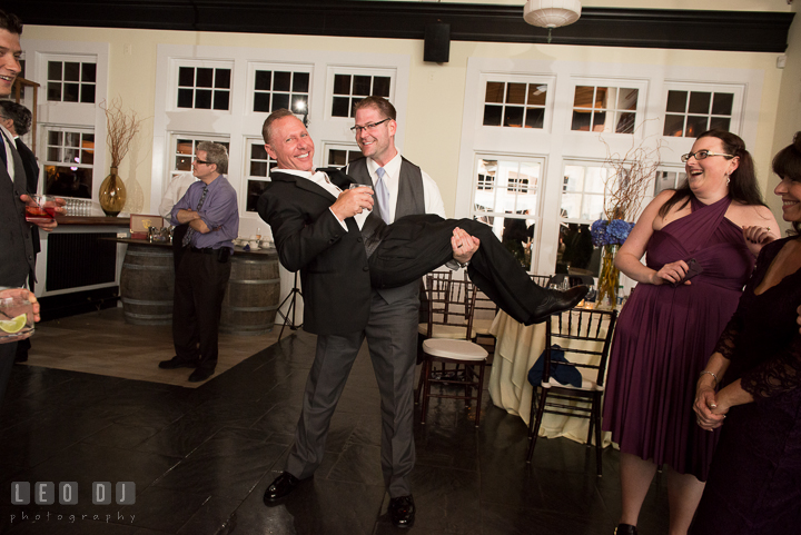 Groom picked up and carried one of the male guests. Kent Island Maryland Chesapeake Bay Beach Club wedding reception party photo, by wedding photographers of Leo Dj Photography. http://leodjphoto.com