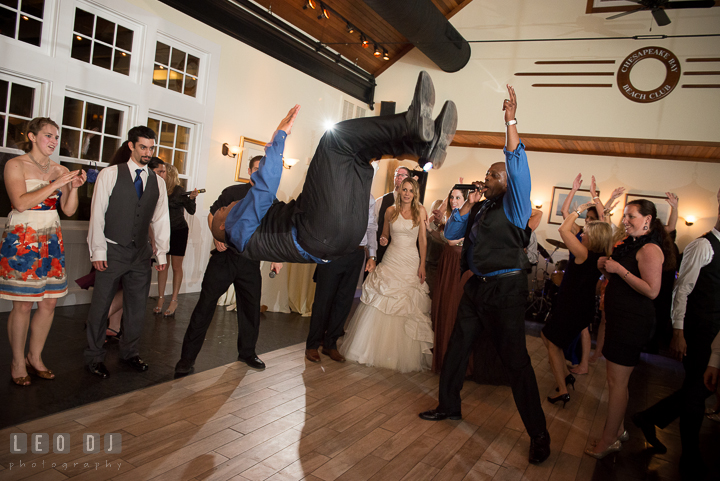 One of the male singer from Onyx Band jumped in the air. Kent Island Maryland Chesapeake Bay Beach Club wedding reception party photo, by wedding photographers of Leo Dj Photography. http://leodjphoto.com