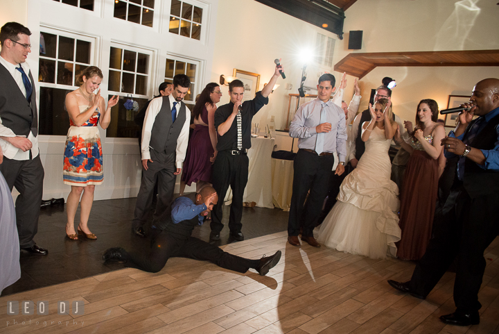 Singer landed with split on ground after somersault jump. Kent Island Maryland Chesapeake Bay Beach Club wedding reception party photo, by wedding photographers of Leo Dj Photography. http://leodjphoto.com