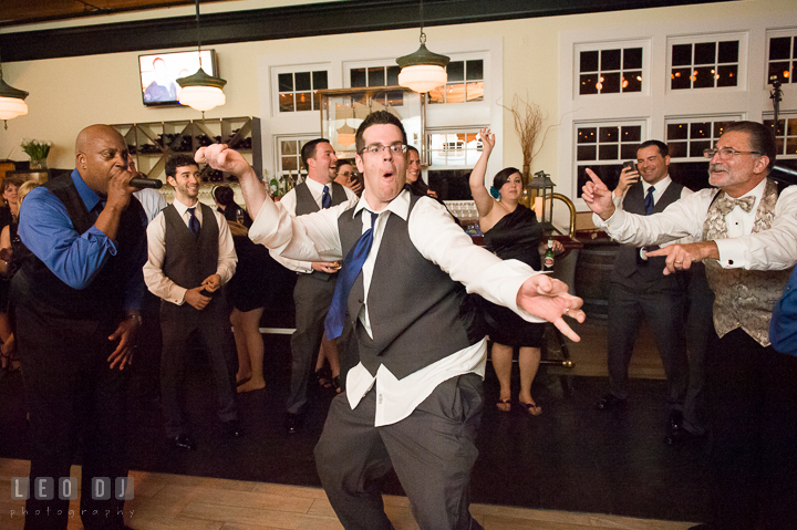 One of Groomsmen doing silly dance pose. Kent Island Maryland Chesapeake Bay Beach Club wedding reception party photo, by wedding photographers of Leo Dj Photography. http://leodjphoto.com
