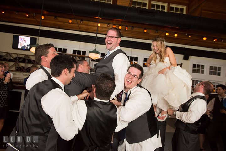 Bride and Groom laughing while being lifted up on chairs. Kent Island Maryland Chesapeake Bay Beach Club wedding reception party photo, by wedding photographers of Leo Dj Photography. http://leodjphoto.com