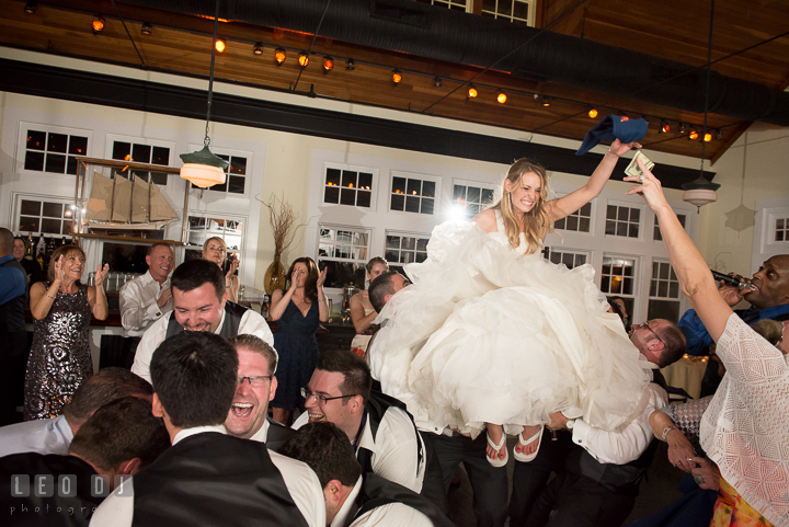 One guests gave money to Bride while being lifted up on chair. Kent Island Maryland Chesapeake Bay Beach Club wedding reception party photo, by wedding photographers of Leo Dj Photography. http://leodjphoto.com