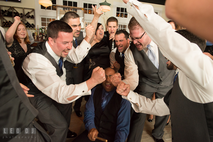Groom and Groomsmen making fists while singing along with band. Kent Island Maryland Chesapeake Bay Beach Club wedding reception party photo, by wedding photographers of Leo Dj Photography. http://leodjphoto.com