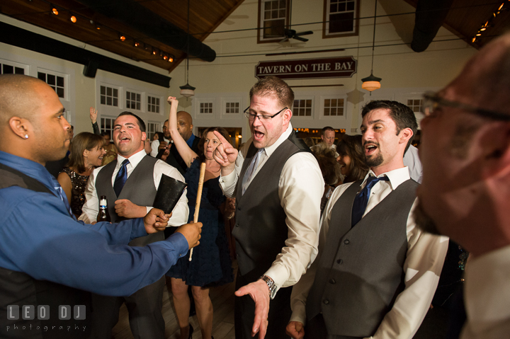 Groom and guests singing while Onyx Band singer plays cowbell percussion. Kent Island Maryland Chesapeake Bay Beach Club wedding reception party photo, by wedding photographers of Leo Dj Photography. http://leodjphoto.com