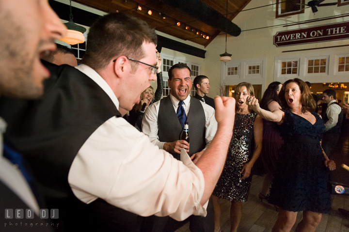 One of Groomsmen singing with another guest and making fists. Kent Island Maryland Chesapeake Bay Beach Club wedding reception party photo, by wedding photographers of Leo Dj Photography. http://leodjphoto.com