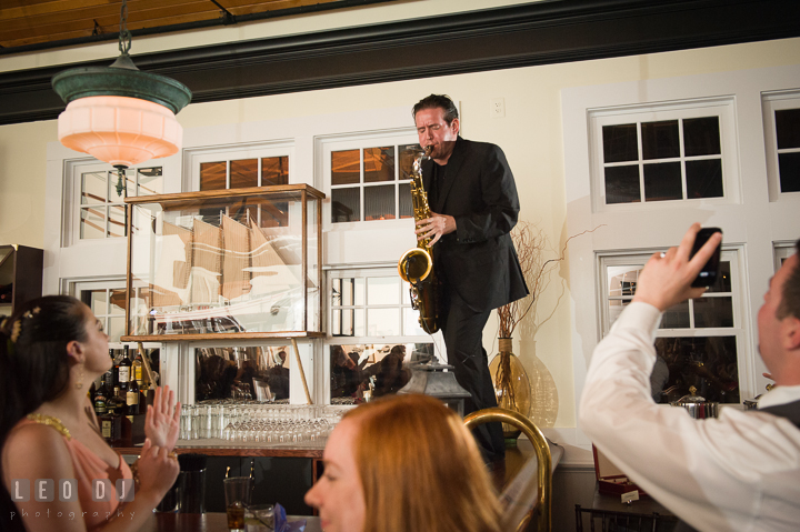 Onyx Band band member standing on top of bar and playing saxophone. Kent Island Maryland Chesapeake Bay Beach Club wedding reception party photo, by wedding photographers of Leo Dj Photography. http://leodjphoto.com