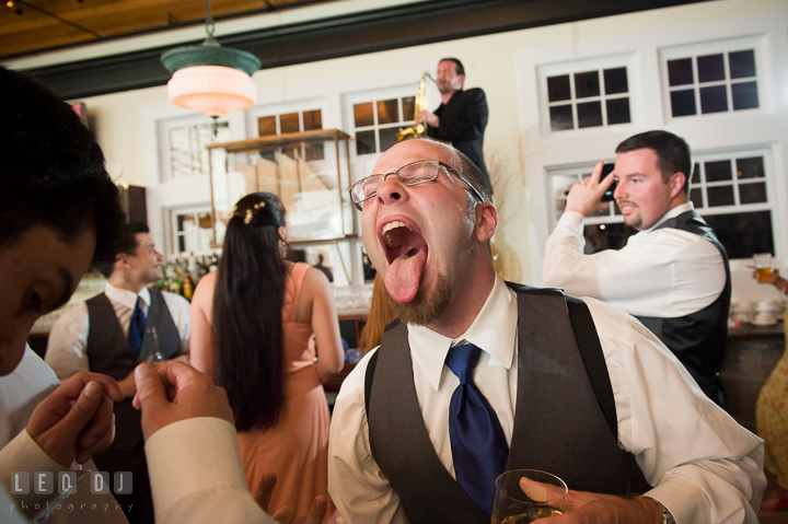 One of Groomsment sticking out his tounge. Kent Island Maryland Chesapeake Bay Beach Club wedding reception party photo, by wedding photographers of Leo Dj Photography. http://leodjphoto.com