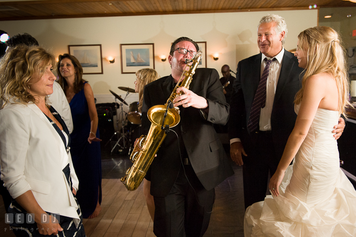 Bride and guests watching Onyx Band's saxophonist perform. Kent Island Maryland Chesapeake Bay Beach Club wedding reception party photo, by wedding photographers of Leo Dj Photography. http://leodjphoto.com
