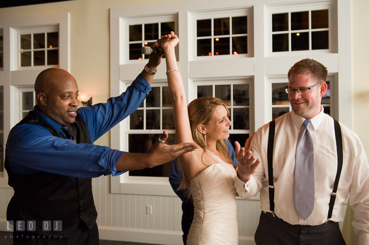 Onyx Band singer lift up Bride's hand. Kent Island Maryland Chesapeake Bay Beach Club wedding reception party photo, by wedding photographers of Leo Dj Photography. http://leodjphoto.com