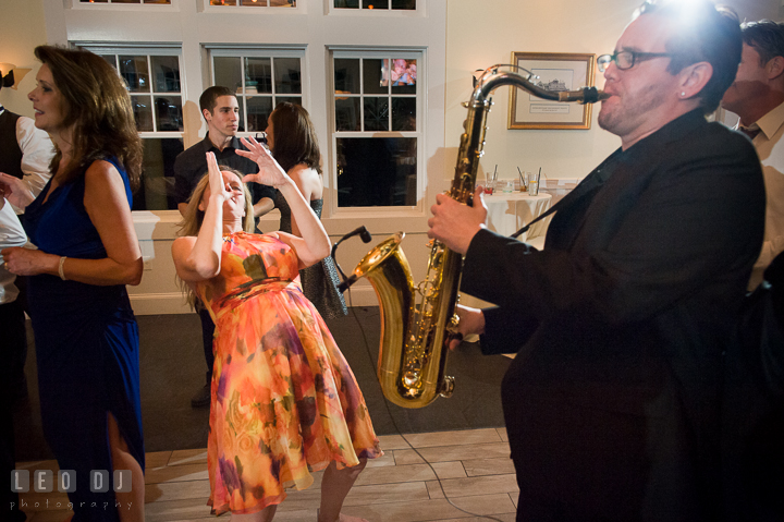 A lady guest immitating saxophone player. Kent Island Maryland Chesapeake Bay Beach Club wedding reception party photo, by wedding photographers of Leo Dj Photography. http://leodjphoto.com