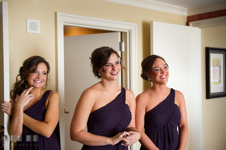 Bridesmaids looking at Bride wearing wedding dress. Getting ready wedding photos at Baltimore Marriott Waterfront by photographers of Leo Dj Photography. http://leodjphoto.com