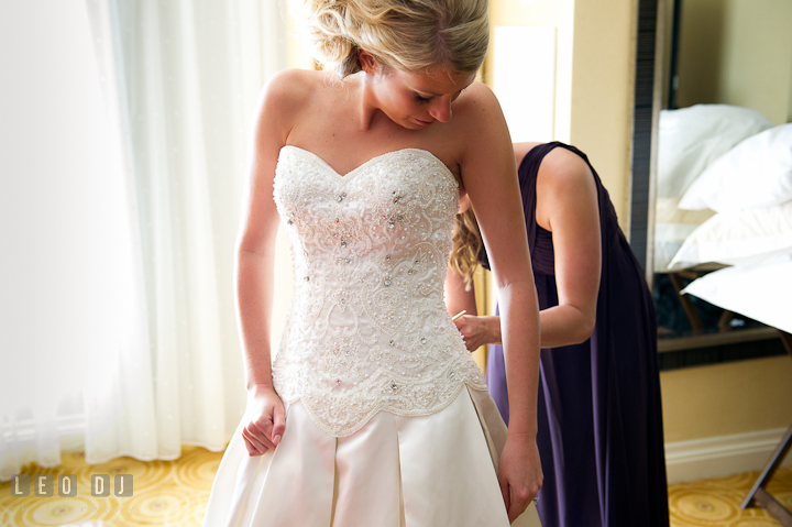 Matron of Honor buttoning up Bride's dress. Getting ready wedding photos at Baltimore Marriott Waterfront by photographers of Leo Dj Photography. http://leodjphoto.com