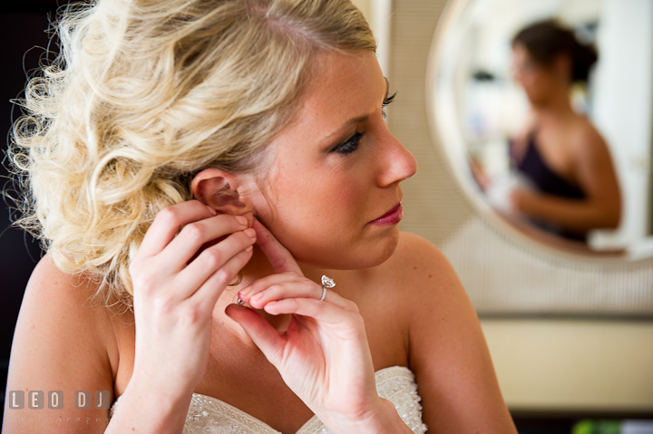 Bride putting on her earrings. Getting ready wedding photos at Baltimore Marriott Waterfront by photographers of Leo Dj Photography. http://leodjphoto.com