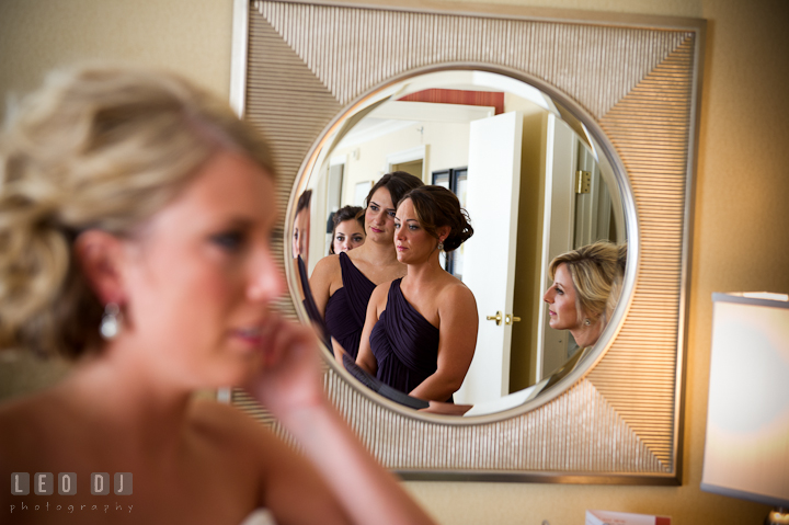 Matron of Honor and Bridesmaids looking at Bride wearing earrings. Getting ready wedding photos at Baltimore Marriott Waterfront by photographers of Leo Dj Photography. http://leodjphoto.com