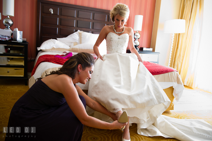 Bridesmaid help Bride put on shoes. Getting ready wedding photos at Baltimore Marriott Waterfront by photographers of Leo Dj Photography. http://leodjphoto.com
