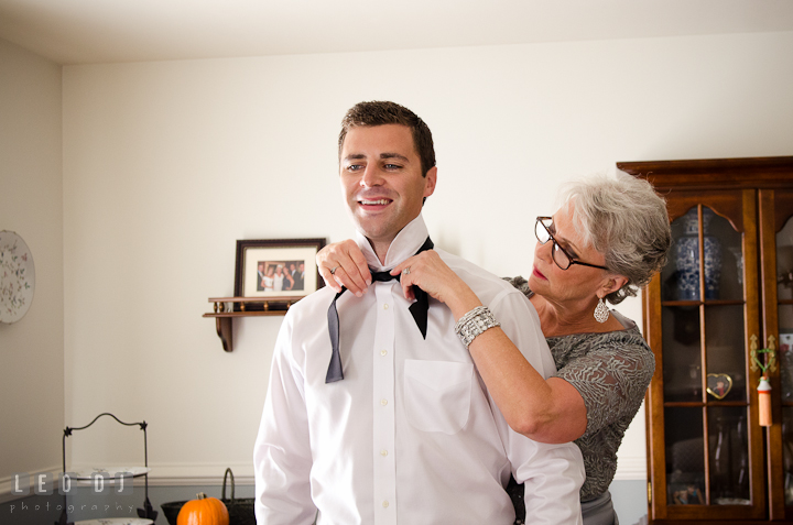 Mother of Groom help son put on bow tie. Getting ready wedding photos at Baltimore Marriott Waterfront by photographers of Leo Dj Photography. http://leodjphoto.com