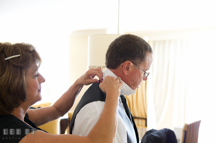 Mother of Bride put on tie for her husband. Getting ready wedding photos at Baltimore Marriott Waterfront by photographers of Leo Dj Photography. http://leodjphoto.com