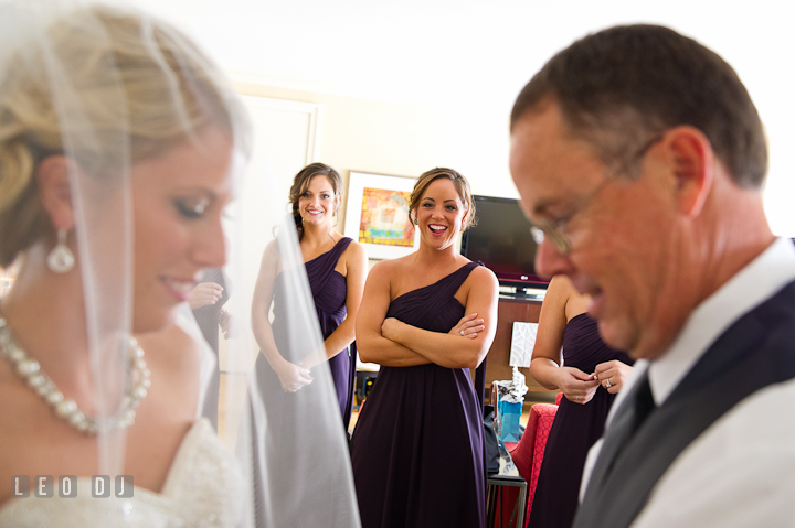 Bridesmaid smiling seeing Father of Bride practice open Bride's veil. Getting ready wedding photos at Baltimore Marriott Waterfront by photographers of Leo Dj Photography. http://leodjphoto.com