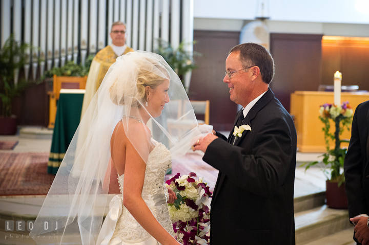 Father of Bride opening daughter's veil. Ceremony wedding photos at Sacred Heart Church, Glyndon, Maryland by photographers of Leo Dj Photography. http://leodjphoto.com